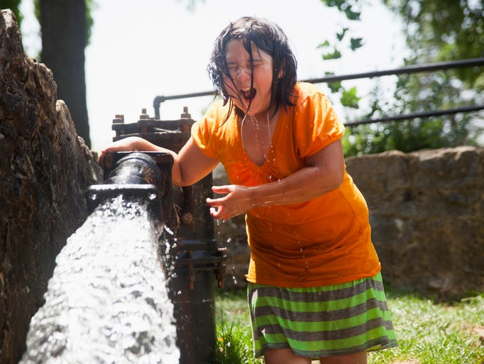 Soyla Hicks, 8, reacts to dunking her head in chilly water alongside a small river at Gypsy Hill Park on Wednesday, July 2, 2014.