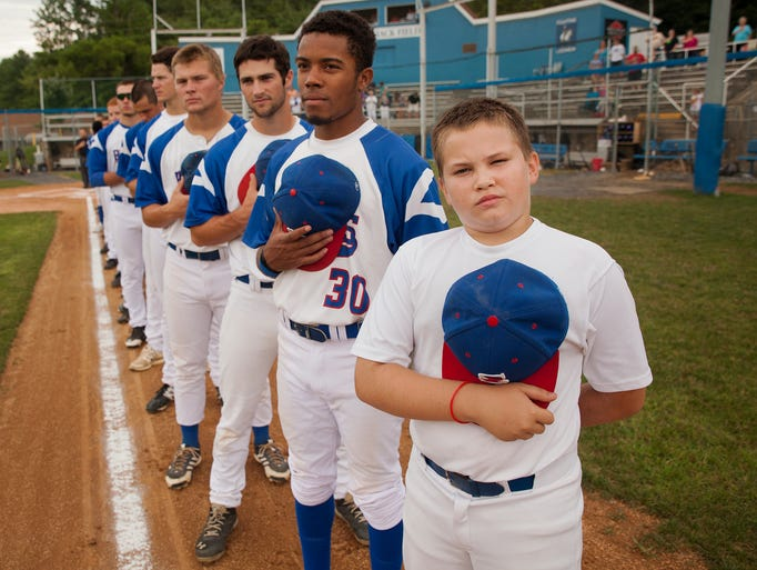 The Staunton Braves' ball boy, Cody Minter, 11, stands next to Michael Smith and other players during the National Anthem before the start of their game against the Waynesboro Generals in Staunton on Sunday, July 27, 2014.