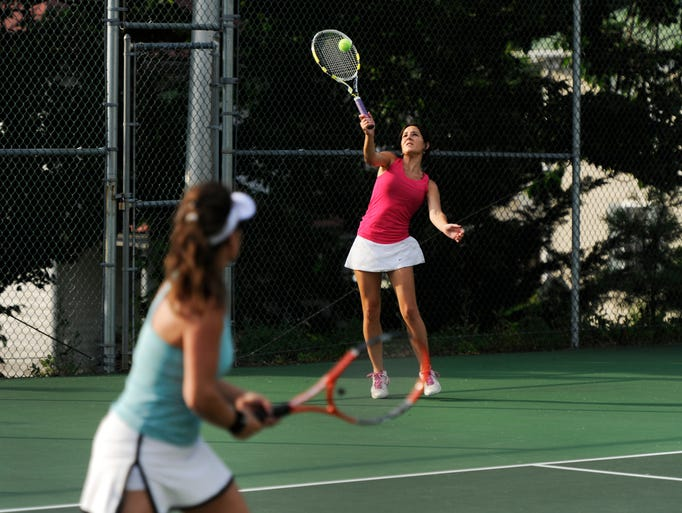 Holly Stambaugh serves the ball as her teammate, Leslie Hock, looks on during the championship women's open doubles match in the Augusta Health/News Leader Tennis Tournament at Mary Baldwin College on Wednesday, July 30, 2014.
