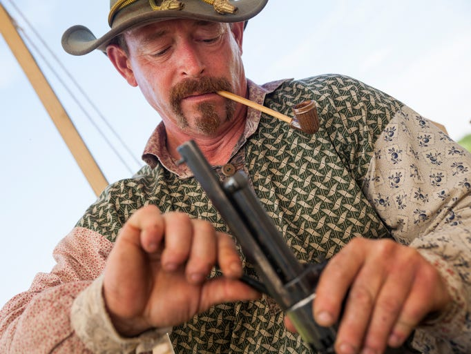 John Freeman, portraying a Confederate Civil War soldier from the 10th Regiment, Virginia Cavalry, demonstrates how he loads his pistol during a reenactment to commemorate the 150th and 149th anniversaries of the first and second battles of Waynesboro at Coyner Springs Park on Sunday, Aug. 31, 2014.