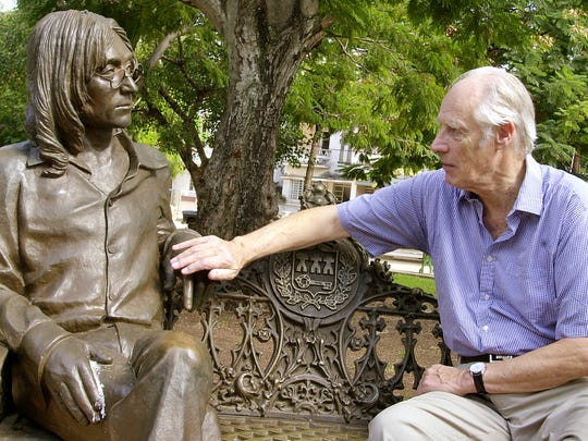 FILE - In this Oct. 30, 2002, file photo, Beatles producer George Martin touches a statue of John Lennon in a park in the Vedado neighborhood of Havana, during his visit to Cuba. George Martin, the producer who guided the Beatles to astounding heights, has died, his manager said on March 9, 2016. He was 90. (AP Photo/Cristobal Herrera, File)