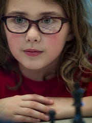 Oak Hill Elementary School 2nd-grader Lydia Gossett, 7, awaits the next move of her opponent at the North Junior High School Spring Scholastic Chess Tournament Saturday afternoon.