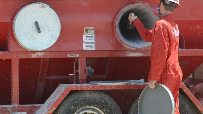 A worker uses a hammer to loosen dust in a particulate filter at a fracking station near Dacono during a May 19 oilfield tour hosted by Anadarko Petroleum Corporation and Coloradans for Responsible Energy Development.