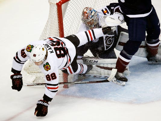 Chicago Blackhawks right wing Patrick Kane, left, careens off Colorado Avalanche goalie Semyon Varlamov, of Russia, after Varlamov stopped his shot in overtime of an NHL hockey game Thursday, Dec. 31, 2015, in Denver. Chicago won 4-3. (AP Photo/David Zalubowski)