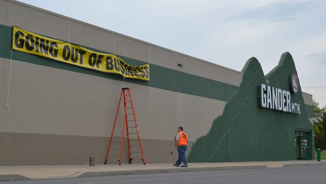 Workers hang a 'going out of business' sign at the Gander Mountain Company store in West Manchester Township on Thursday.