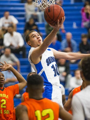 Michael Bibby of Shadow Mountain High School goes up for two against Corona del Sol players Saben Lee, left, (2) and Dalen Dorsey (12)             during game at Shadow Mountain High School, Monday, January 18, 2016.