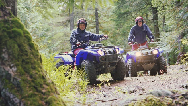 Couple riding ATV's through forest