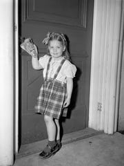In this 1947 photo, a little girl identified as Connie Wear of Lakewood, Wis., hangs a May basket that she made in nursery school.