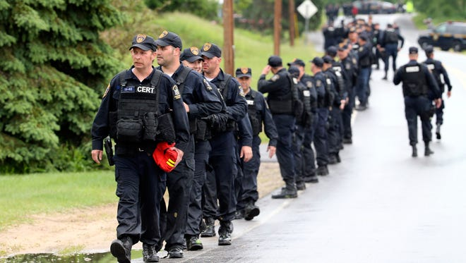 Law enforcement officers walk along Trudeau Road at Route 3 after emerging from the woods during a search for two escapees from Clinton Correctional Facility on Friday, June 12, 2015, near Dannemora, N.Y. Squads of law enforcement officers are searching for David Sweat and Richard Matt, two murderers who escaped from the maximum-security prison in northern New York.