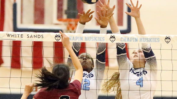 El Dorado's Brianna Valdez, 3, hits the ball against outstretched hands of Chapin's Kayla Ulmer, 12, and Amelia Crossley, 4, Tuesday night at Chapin. The Huskies won in four sets.