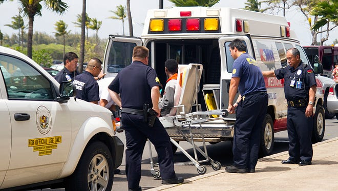 A 15-year-old boy, seen sitting on a stretcher, who stowed away in the wheel well of a flight from San Jose, Calif., to Maui is loaded into an ambulance at Kahului Airport in Kahului, Maui, Hawaii.