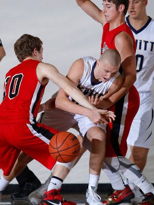 DeWitt's Tanner Reha, center, and St. Johns' Tommy Jury, left, and Jack Bouck fight for the ball Friday, Dec. 18, 2015, in DeWitt, Mich.