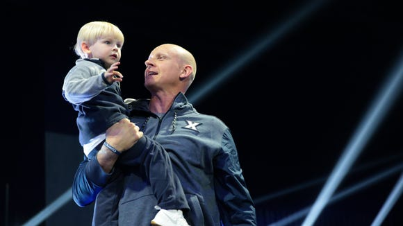 Xavier Musketeers head coach Chris Mack carries his son Brayden as he's introduced during Musketeer Madness, Friday, Oct. 20, 2017, at Cintas Center in Cincinnati.