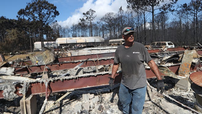 Mike Thornburg searches through the debris of his family home for salvagable belongings Tuesday in Eastpoint, Fla. where a wildfire, still smoldering, ripped through the area consuming more than 30 homes.