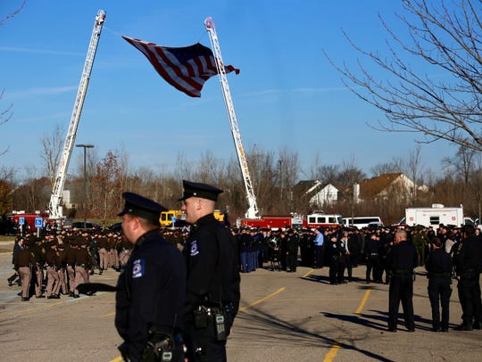 Officers line up outside the funeral service for Oakland County Sheriff's Deputy Eric Overall.
