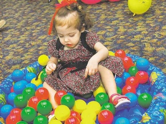 Kylie Walleser-Bush plays in a small pool of plastic balls while celebrating her second birthday and one-year anniversary of her small-bowel transplant.