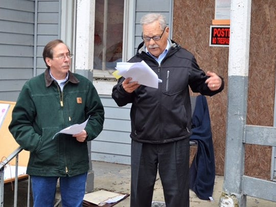 David Kleinfelter, of Kleinfelter's Auction, Inc., of Lebanon, listens as Myerstown Borough Solicitor Frederick Wolf announces to the crowd the conditions of sale for the historic Coover Mansion during the mansion's auction on Wednesday, Nov. 1.