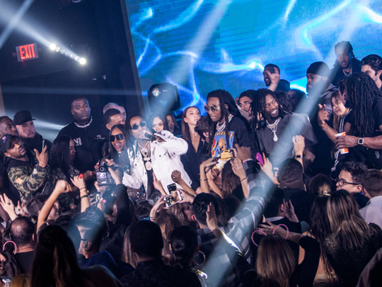 The Henry family stands onstage with Migos while they perform.