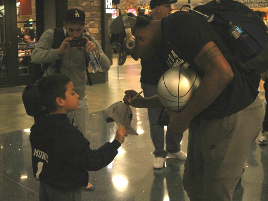 Wolf Pack basketball player Jordan Caroline signs a cap for 8-year-old fan Isaiah Muñoz on Sunday at the Reno-Tahoe International Airport.