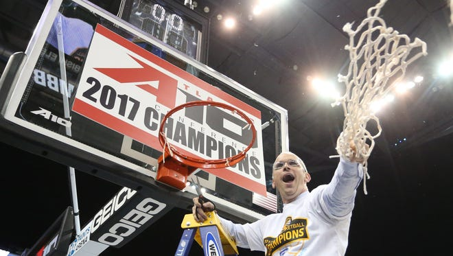 Rhode Island Rams head coach Dan Hurley  cutting the net after his team's victory over Virginia Commonwealth in the Atlantic 10 Conference championship game in Pittsburgh.