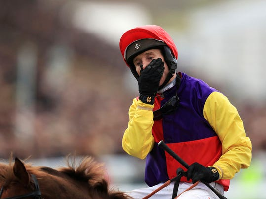 Jockey Richard Johnson riding Native River gestures after winning the Cheltenham Gold Cup, during the 2018 Cheltenham Festival at Cheltenham Racecourse, in Cheltenham, England, Friday March 16, 2018. (Mike Egerton/PA via AP)