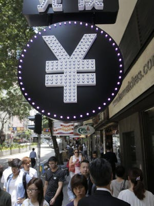 A Chinese yuan sign is seen at a currency exchange shop in Hong Kong on Aug. 11.