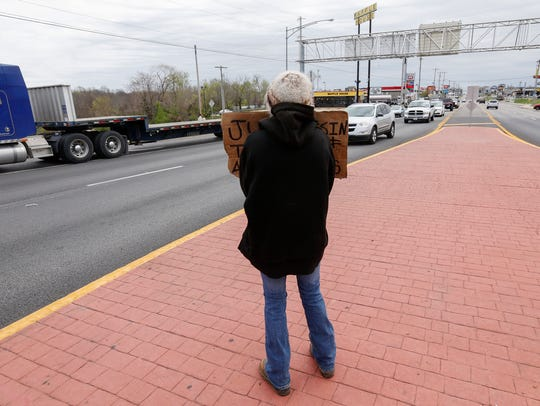 Alexis holds up a sign while panhandling near the I-44