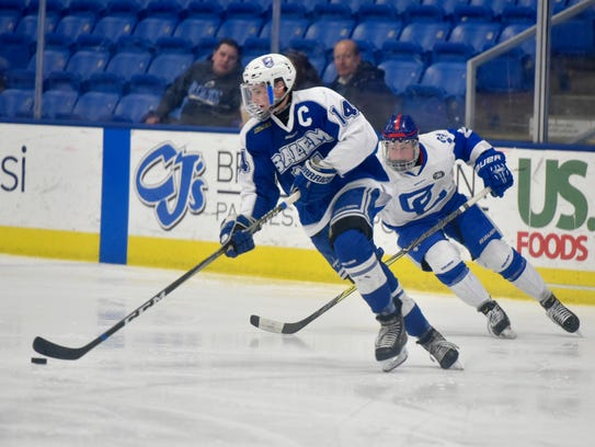 Salem senior forward Tyler German (14) tries to stay a step ahead of a Novi Detroit Catholic Central Thursday night at USA Hockey Arena in Plymouth.