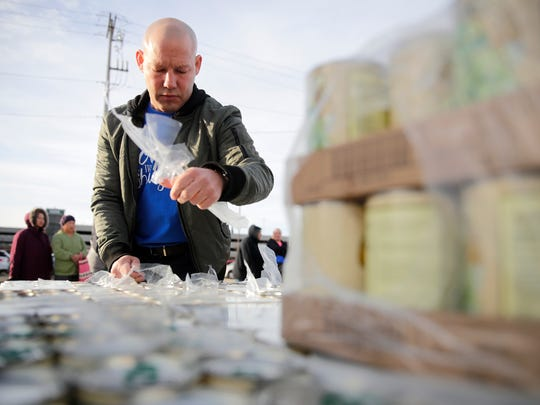 Chris Stegman, president of USA TODAY NETWORK-Wisconsin and a Stock the Shelves mobile pantry volunteer, opens the packaging for canned goods while preparing for the mobile pantry Thursday, Oct. 19, 2017, in Appleton, Wis.