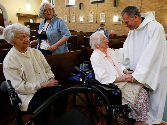 Sister Regina Rose Palkovics, a Sister of Charity of Saint Elizabeth gets birthday wishes from Father Anthony Sargent, O.S.B. after morning mass as her sister, Sister Maria Anne Palkovics, l, and niece Dorothy Germain of Virginia look on. Sister Regina turned 105 today at The Villa at Florham Park. June 7, 2018. Florham Park, NJ