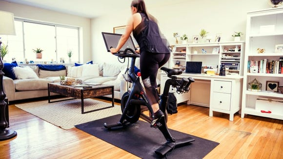 Reviewed's Director of Audience, Samantha Matt, riding the Peloton in her home.