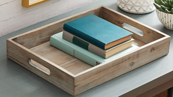 Stack this wooden tray with books and a decorative candle.