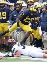 Michigan's Karan Higdon runs by Ohio State's Tuf Borland on Nov. 25, 2017.