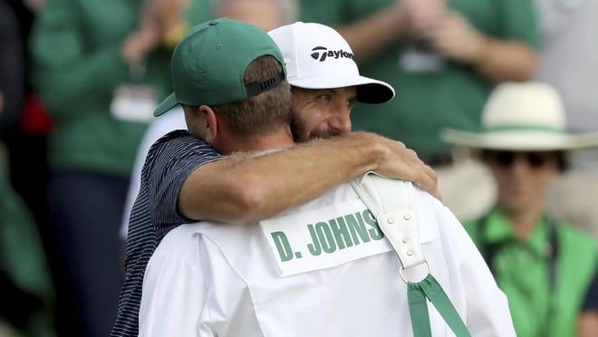 Dustin Johnson reacts with his brother and caddie Austin Johnson on the 18th green after winning the Masters on Sunday in Augusta, Ga.