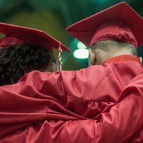 Two Everett graduates wrap arms after receiving their diplomas at their graduation ceremony Saturday, May 30, 2015.