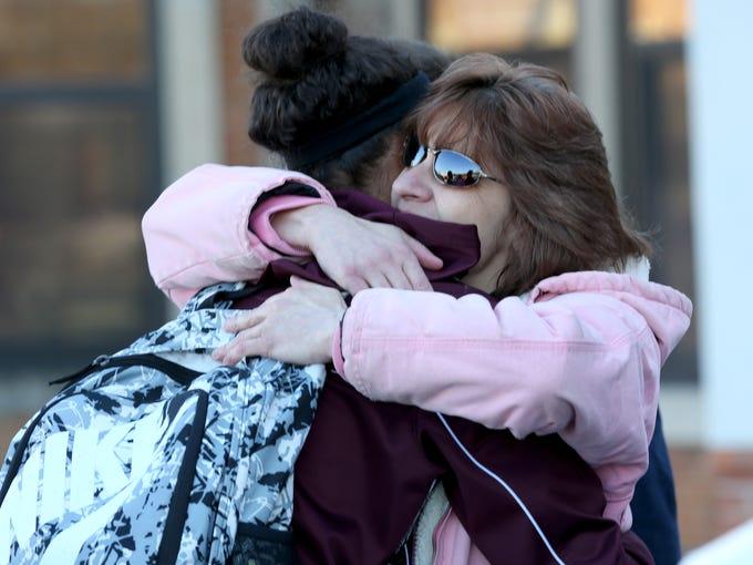 Fatimaah Findley hugs Sarah Taft at a remembrance service