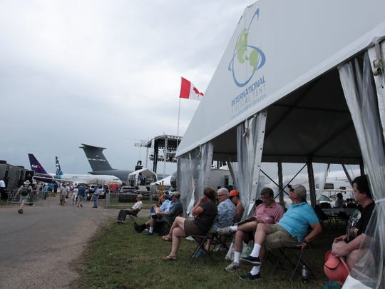 EAA AirVenture attendees watch the air show from the International Visitors Tent Wednesday in Oshkosh.