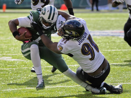 Jets quarterback Geno Smith is sacked by Ravens linebacker