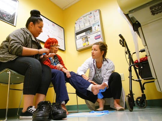 Reyna Medina helps interpret her grandmother Juanita Montes Spanish to English for nurse practitioner Hannah Hewes while she examined her for issues with her diabetes at Westside Family Healthcare.