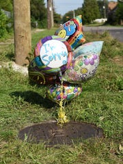 Balloons are tied to the manhole cover at the site where a body was found in a sewer near Chalfonte and Steel Streets in Detroit.