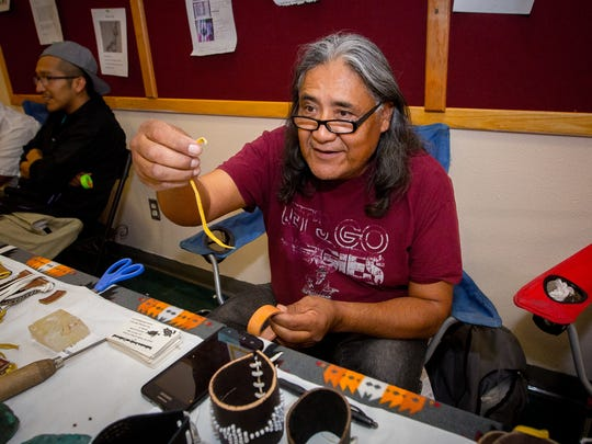 "Joseph ""Joe"" Trujillo works on his leather craft during the Native American Arts & Crafts Expo."