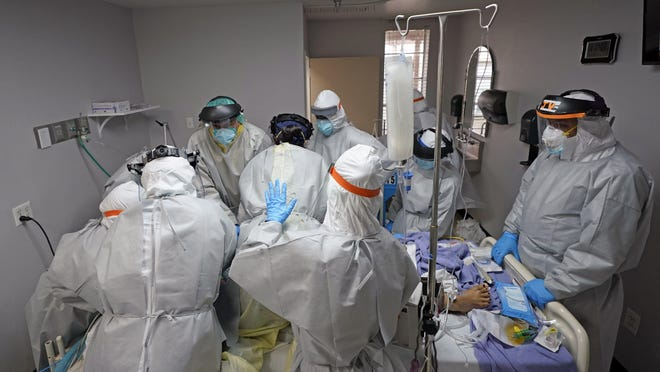Doctors try to save the life of a patient inside the Coronavirus Unit at United Memorial Medical Center, Monday, July 6, 2020, in Houston. This patient later died.