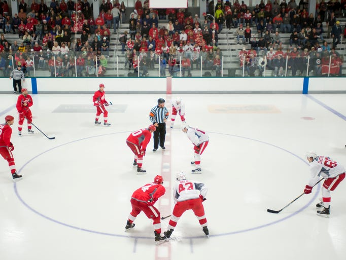 Red Wings players line up for afaceoff during a training-camp scrimmage on Saturday, Sept. 20, 2014 in Traverse City.