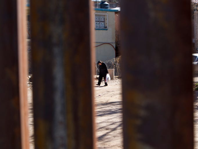 Seen through the border fence, a resident walks through the Buenos Aires neighborhood in Nogales, Sonora. This area accounted for one-sixth of all incidents across the nearly 2,000-mile U.S.-Mexico border in which Border Patrol agents responded to rock-throwing with force.