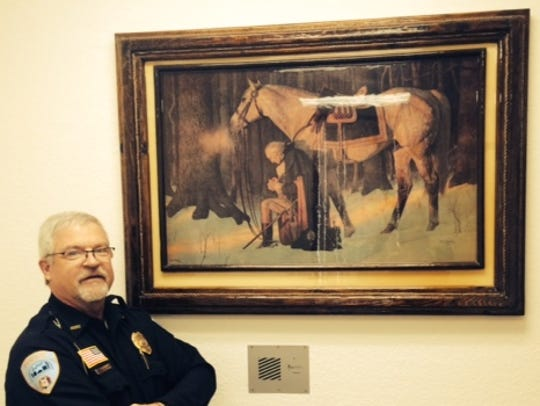 Korey Schillinger stands in front of a painting given