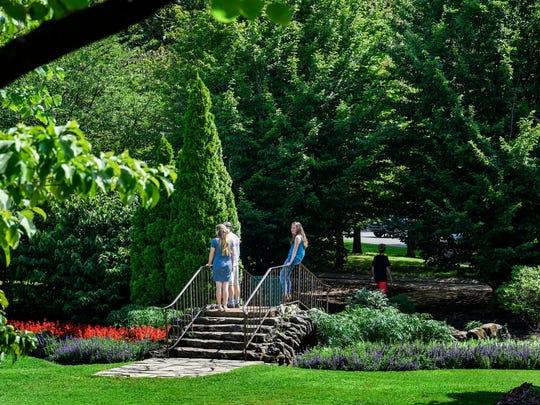 People enjoy the gardens that runs along Centennial