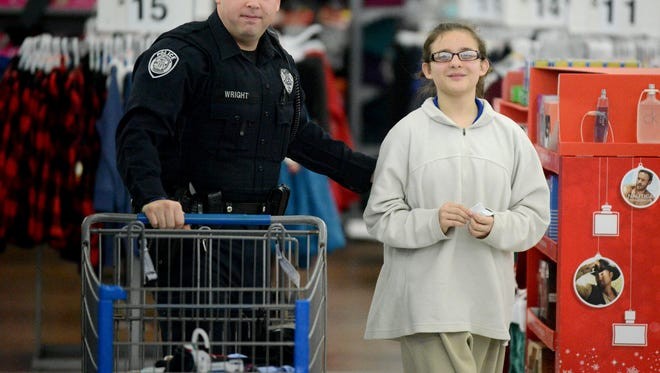 Jackson Police Officer Lance Wright walks 12-year-old Marisa Torres to the register after completing their Shop with a Cop session, Tuesday evening at Wal-Mart.