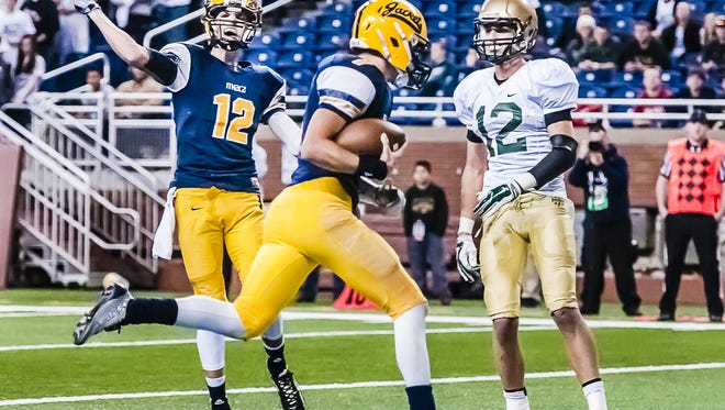 Jake Smith, center, reaches the end zone for a touchdown as teammate Spence DeMull (12) celebrates during last year's state final at Ford Field. Smith has a chance to follow in his brother's footsteps and quarterback the Yellowjackets to a state title.