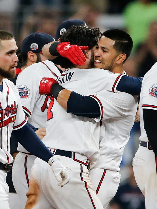 Atlanta Braves' Rio Ruiz (14) embraces Dansby Swanson after driving him in for the game-winning run in the ninth inning of a baseball game against the New York Mets on Friday, June 9, 2017, in Atlanta. Atlanta won 3-2. (AP Photo/John Bazemore)
