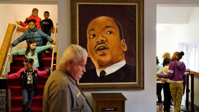 A portrait of Dr. Martin Luther King Jr. hangs in Ebenezer Baptist Church where King preached, as school children tour the historic building during an event celebrating the birthday of the slain civil rights icon in Atlanta, Friday, Jan. 12, 2018. A federal holiday to commemorate his birthday is observed Monday, Jan. 15. (AP Photo/David Goldman) ORG XMIT: GADG101